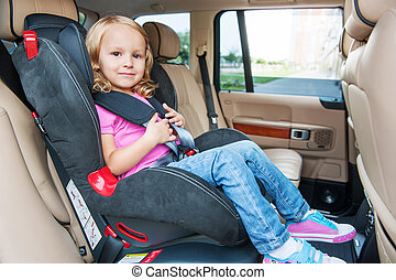 Small girl is sitting in child cat seat, looking at the...