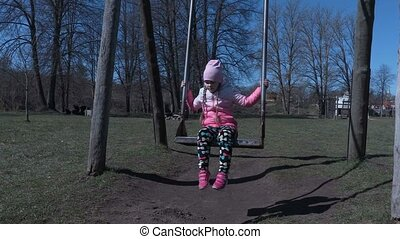 Small girl on swing in the playground