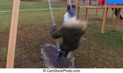 Small girl on swings after school