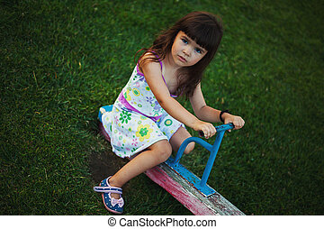 Small Girl on Teeter - Portrait of a small girl on teeter on...