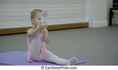 Small girl performs ballet movement in dance studio indoors....