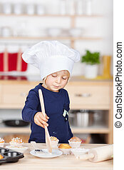 Small girl playing in the kitchen with a chef hat