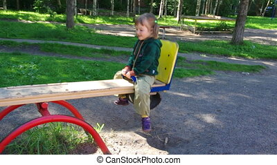 small girl playing on a seesaw