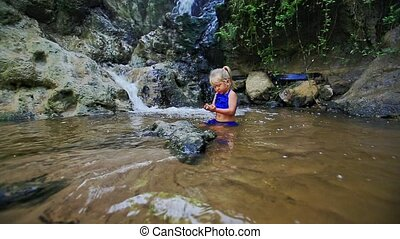 Small Girl Plays in Shallow Transparent Water by Waterfall