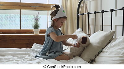 Small girl pretending to be doctor, playing in bedroom alone.