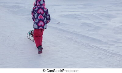 Small girl pushing sled with a doll