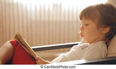 Small girl reading a book in armchair