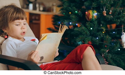 Small girl reading a book in front of Christmas tree