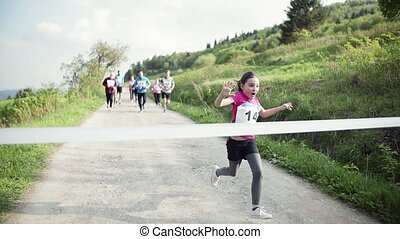 Small girl runner crossing finish line in a race competition...