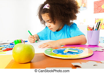 Small girl sits at the table and writing letters