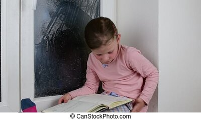 Small girl sits on windowsill behind the frozen window. Cute...