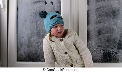 Small girl sits on windowsill behind the frozen window.