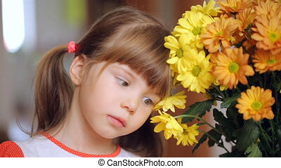 Small girl sitting by the bunch of yellow flowers