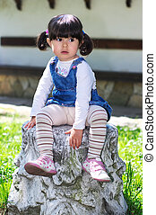 Small girl sitting in the garden