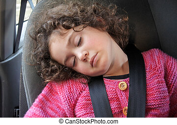 Small girl sleeping in a car seat
