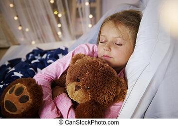 Small girl sleeping with teddy bear