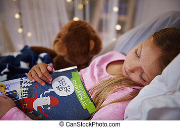 Small girl taking a nap with book and teddy bear
