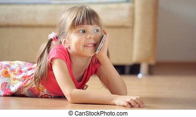 Small girl talking on smartphone lying on floor