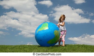 Small girl trying to catch inflatable Earth ball blown by wind on meadow