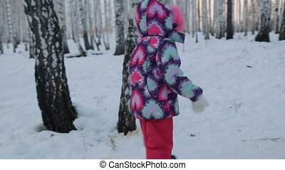 Small girl walking in winter forest