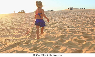 Small Girl Walks Barefooted on Sand Dunes Stops Tired at Sunset