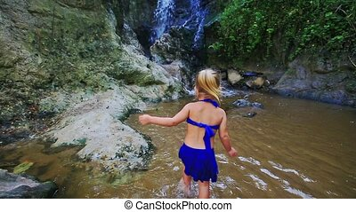 Small Girl Walks in Stream Water to Waterfall