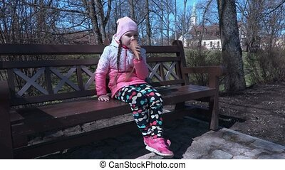 Small girl watching and eating ice cream