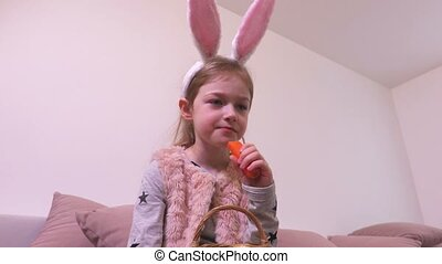 Small girl with bunny ears eating carrot