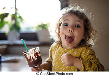 Small girl with dirty mouth indoors in kitchen at home, eating pudding.