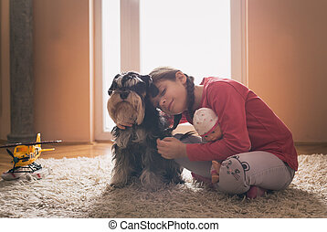 Small girl with dog on carpet