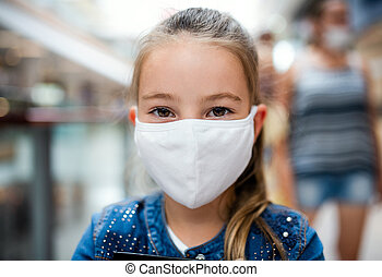 Small girl with face mask looking at camera indoors in ...