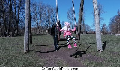 Small girl with father near swing