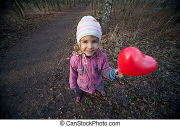 Small girl with inflatable red heart in terrible dark forest