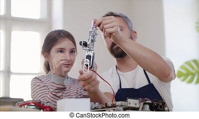 Small girl with man at repair cafe repairing household electrical devices.