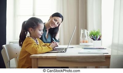 Small girl with mother sitting at table at home, using...