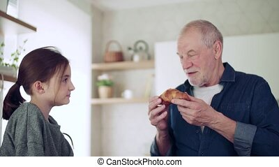 Small girl with senior grandfather indoors in kitchen ...