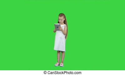 Small girl with tablet computer on a Green Screen, Chroma Key