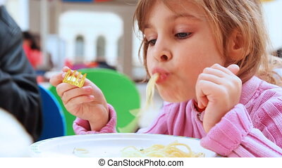 small girl with yellow fork in hands eats pasta