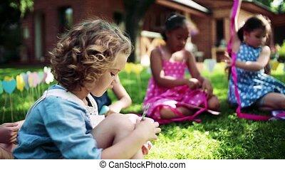 Small girls sitting on ground outdoors in garden in summer, ...