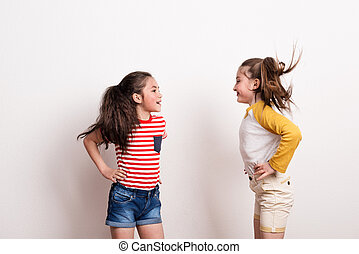 Small girls standing in a studio, looking at each other.