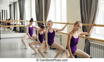 Small girls starting ballet-dancers in leotards are doing...