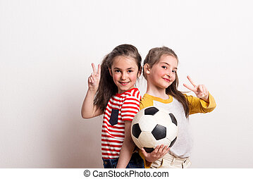 Small girls with a soccer ball standing in a studio, showing victory sign.