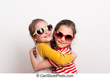 Small girls with sunglasses standing in a studio, hugging.