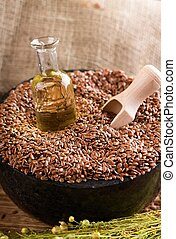 Small glass bottle with flax oil in heap of seeds