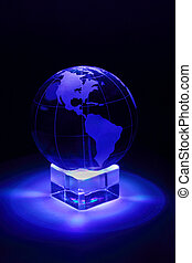 Small glass globe at glass stand is illuminated by blue...