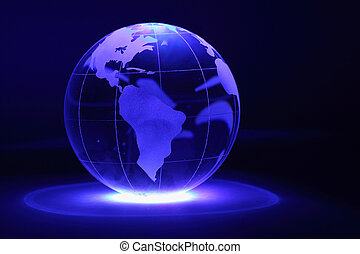 Small glass globe is illuminated by blue light from below in...