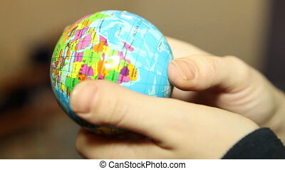 small globe in the hands of women