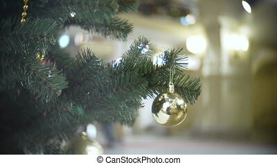 Small golden mirror ball. New Year's and abstract blurred shopping mall background with Christmas tree decorations.