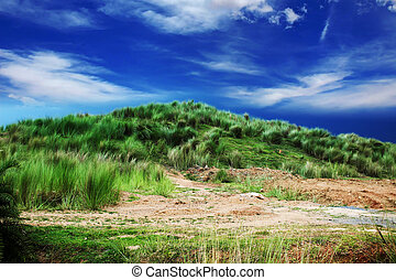 Small grass mountain with colorful cloud sky