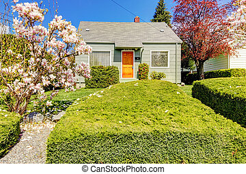 Small green house exterior with spring blooming trees. -...